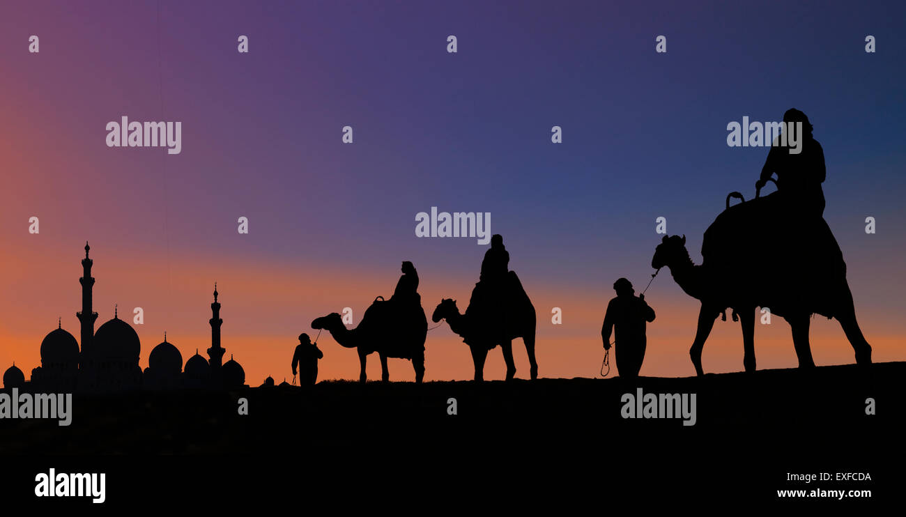 Camel caravan arriving at mosque, Abu Dhabi, United Arab Emirates - Stock Image