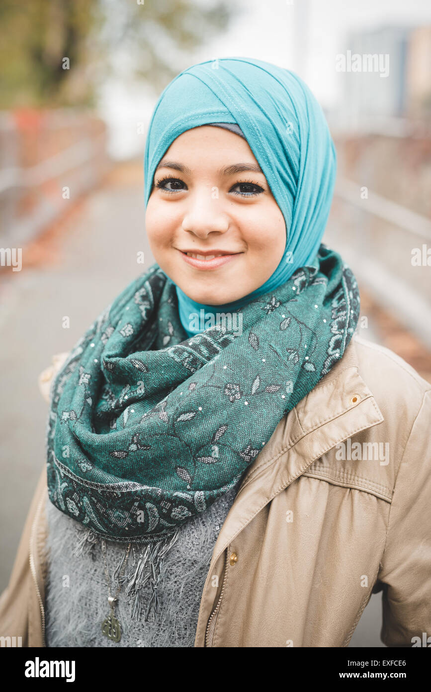 Portrait of young woman wearing turquoise hijab on park path - Stock Image