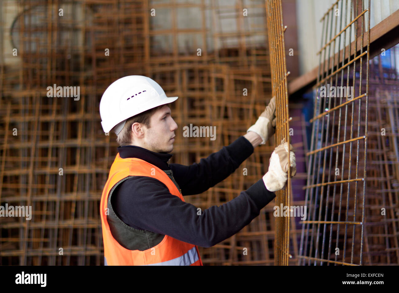 Factory worker moving wire mesh in concrete reinforcement factory Stock Photo