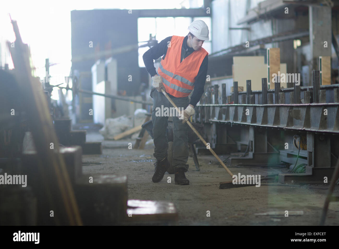 Factory worker sweeping up in concrete reinforcement factory - Stock Image