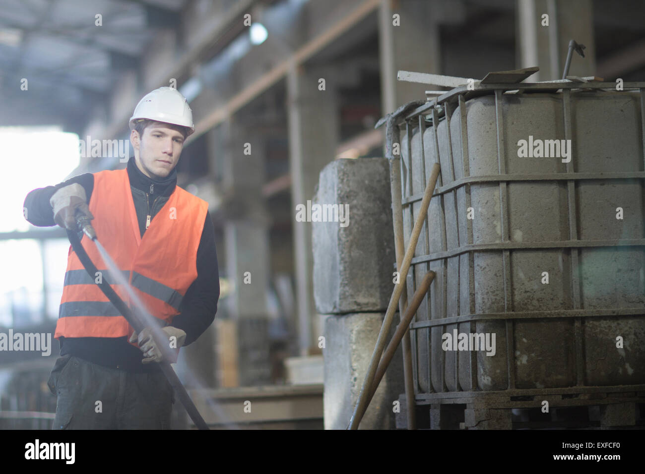 Factory worker cleaning up with water hose in concrete reinforcement factory - Stock Image