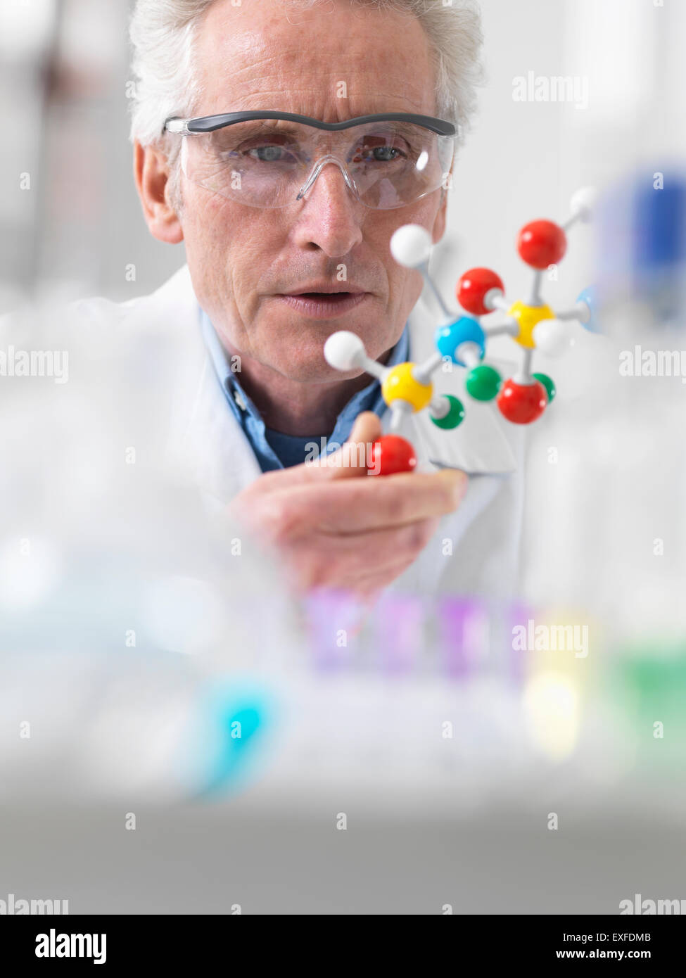 Scientist viewing molecular model of a chemical formula in a laboratory - Stock Image
