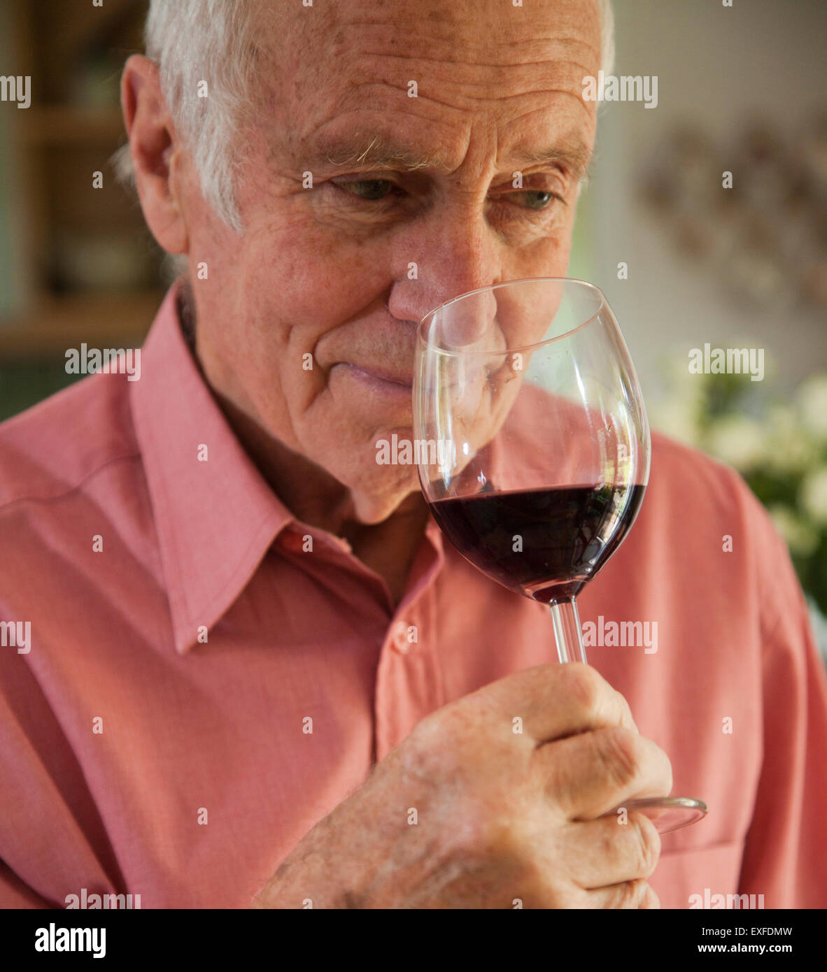 Man smelling aroma of glass of red wine - Stock Image