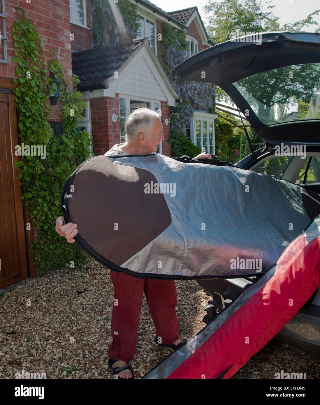 Senior man loading surfboard into car boot - Stock Image