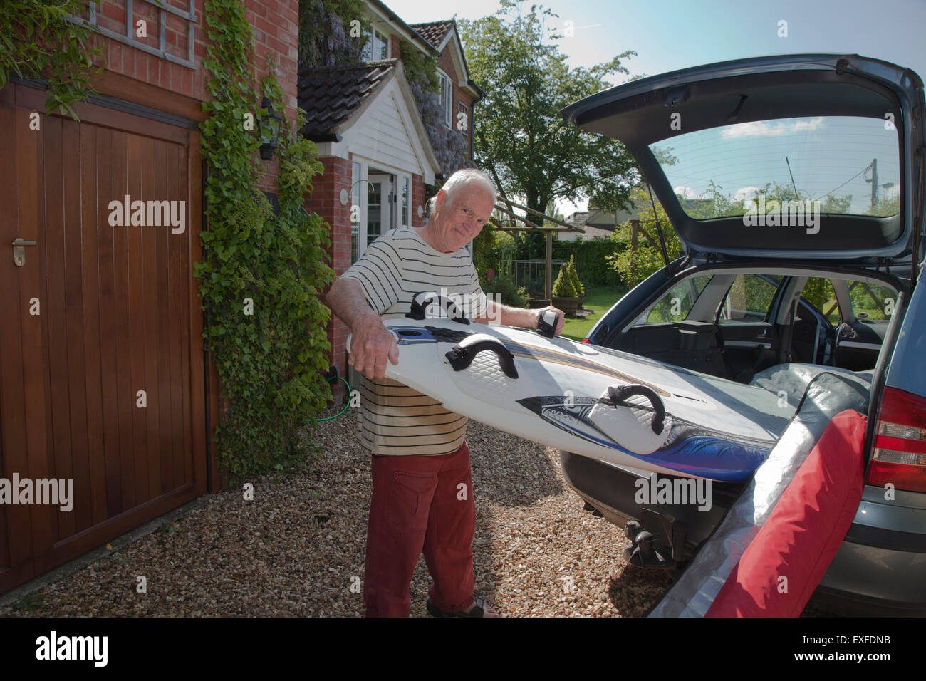 Senior man removing surfboard from car boot - Stock Image
