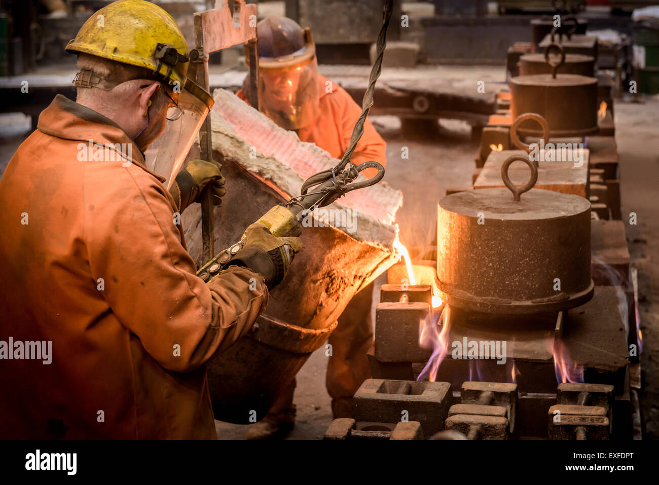 Workers pouring molten metal from flask in foundry - Stock Image