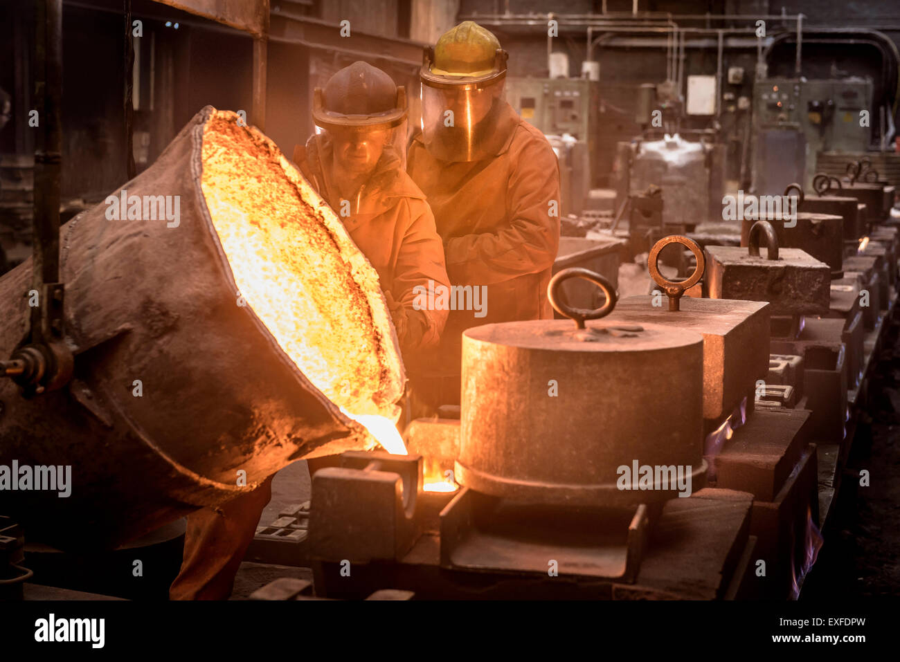 Two workers pouring molten metal from flask in foundry - Stock Image
