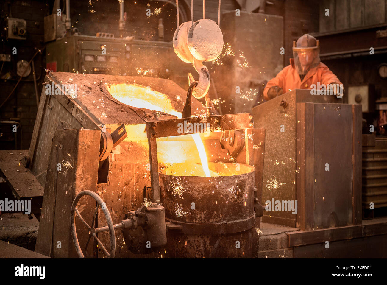Worker pouring molten metal in foundry - Stock Image