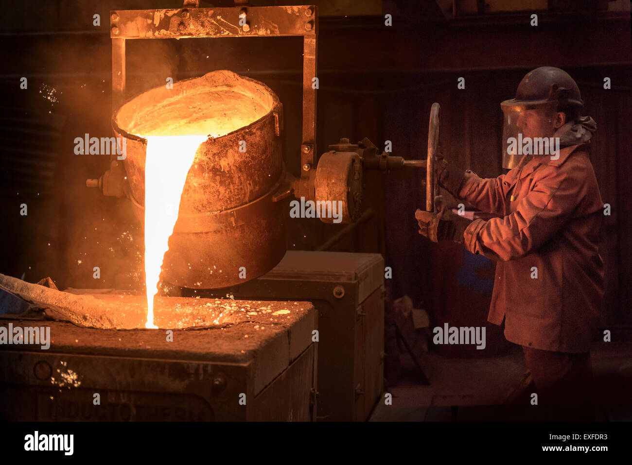Worker pouring molten metal from flask in foundry - Stock Image