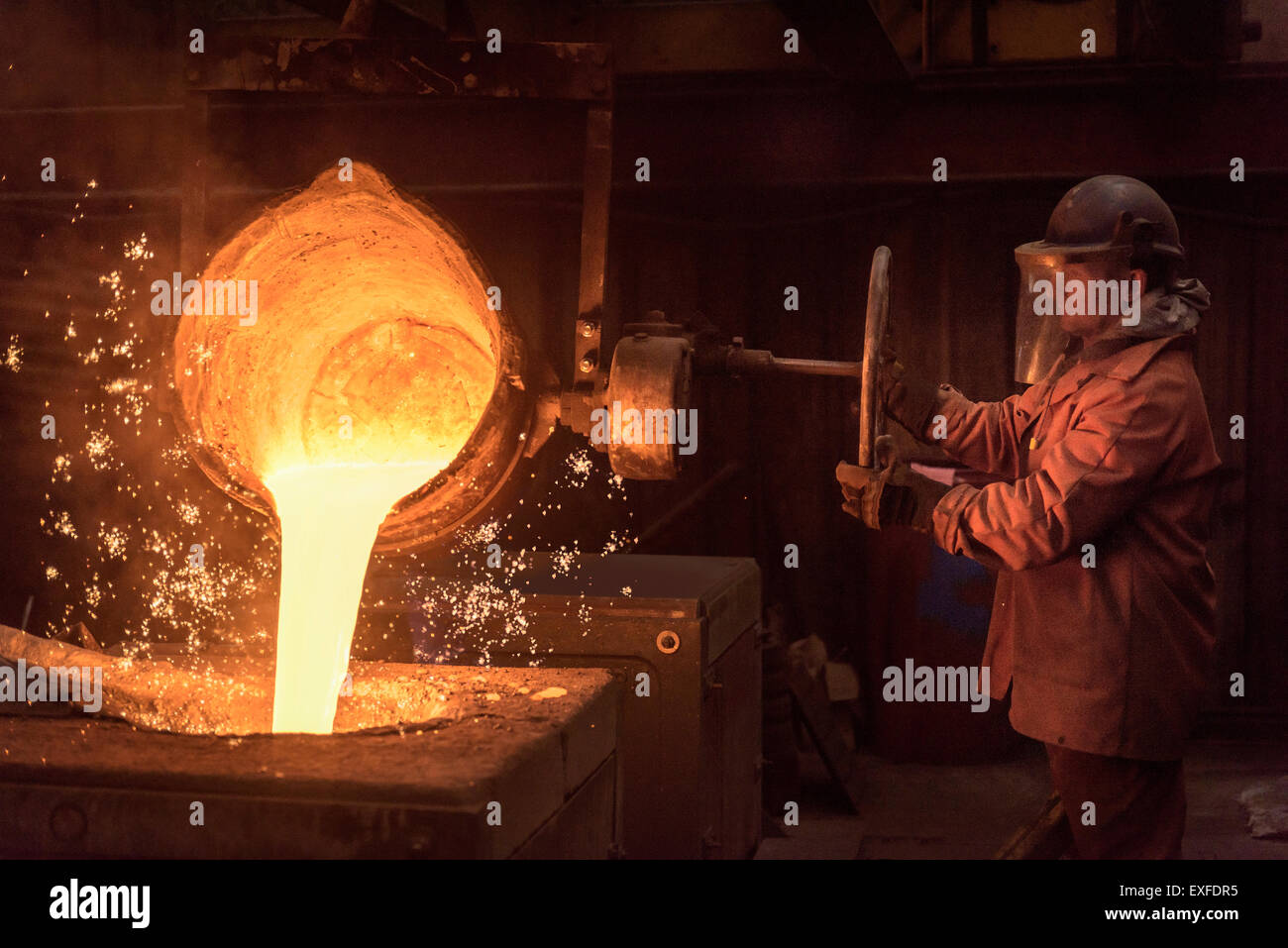 Worker pouring molten metal from flask in foundry workshop - Stock Image