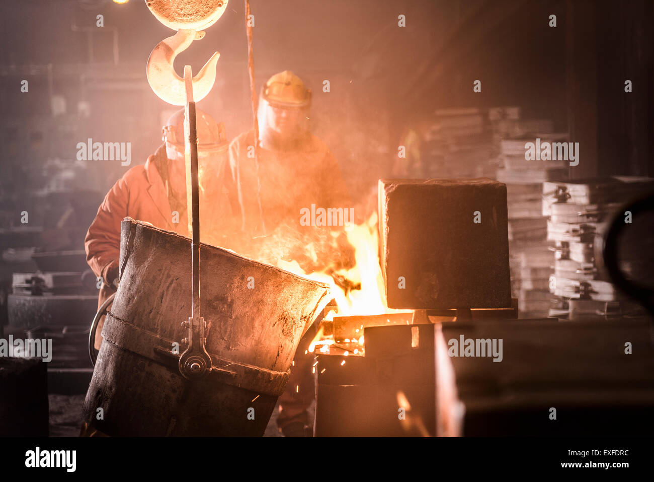 Workers pouring molten metal into moulds from flask in foundry - Stock Image