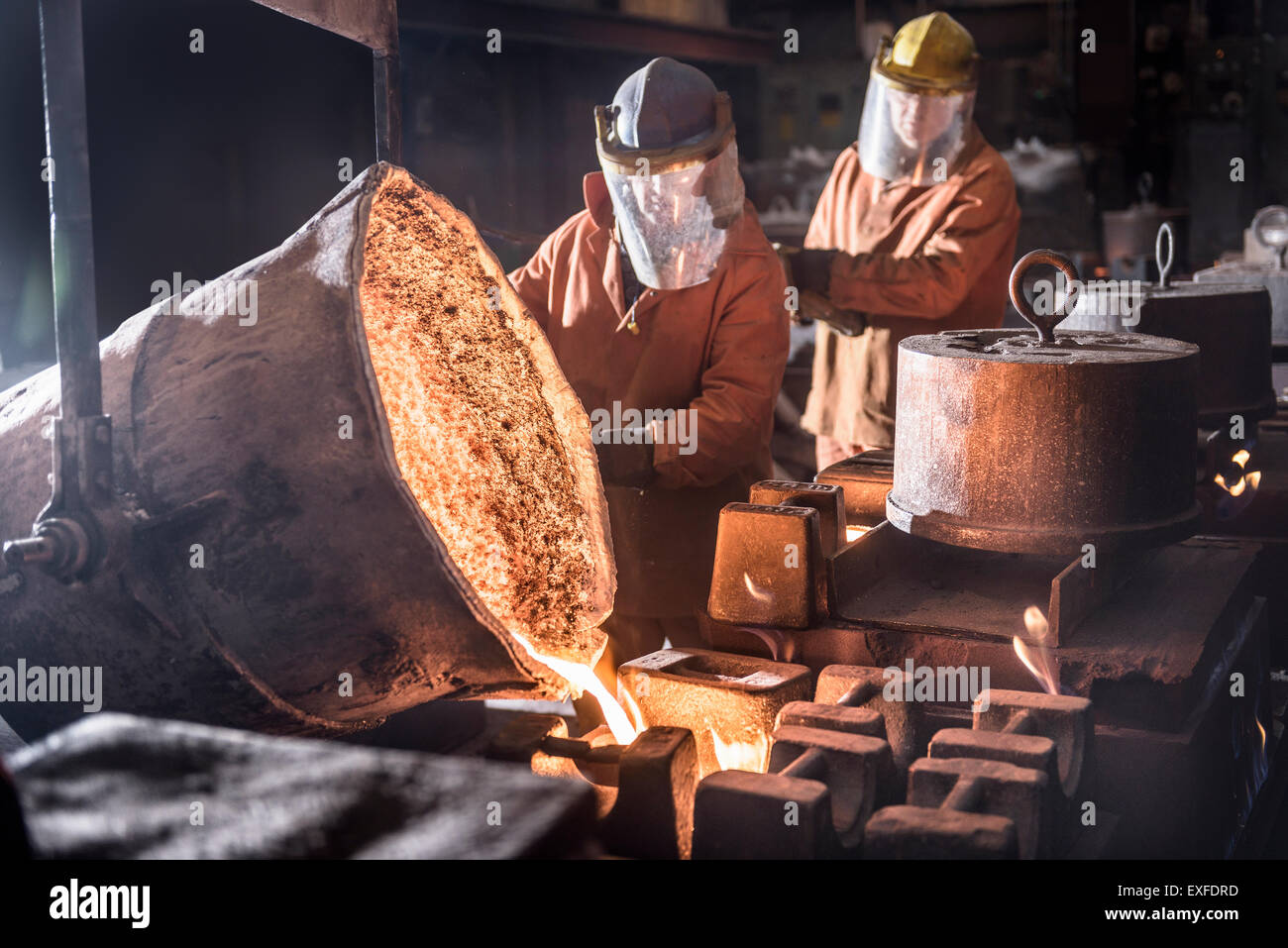 Workers pouring molten metal from flasks into moulds in foundry - Stock Image