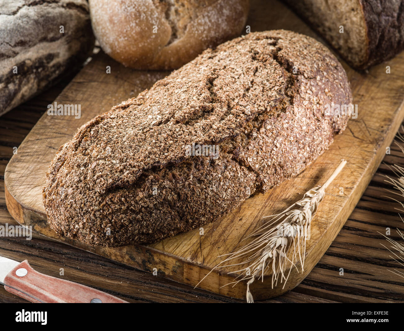 Rye-bread loaf on the wooden plank. - Stock Image