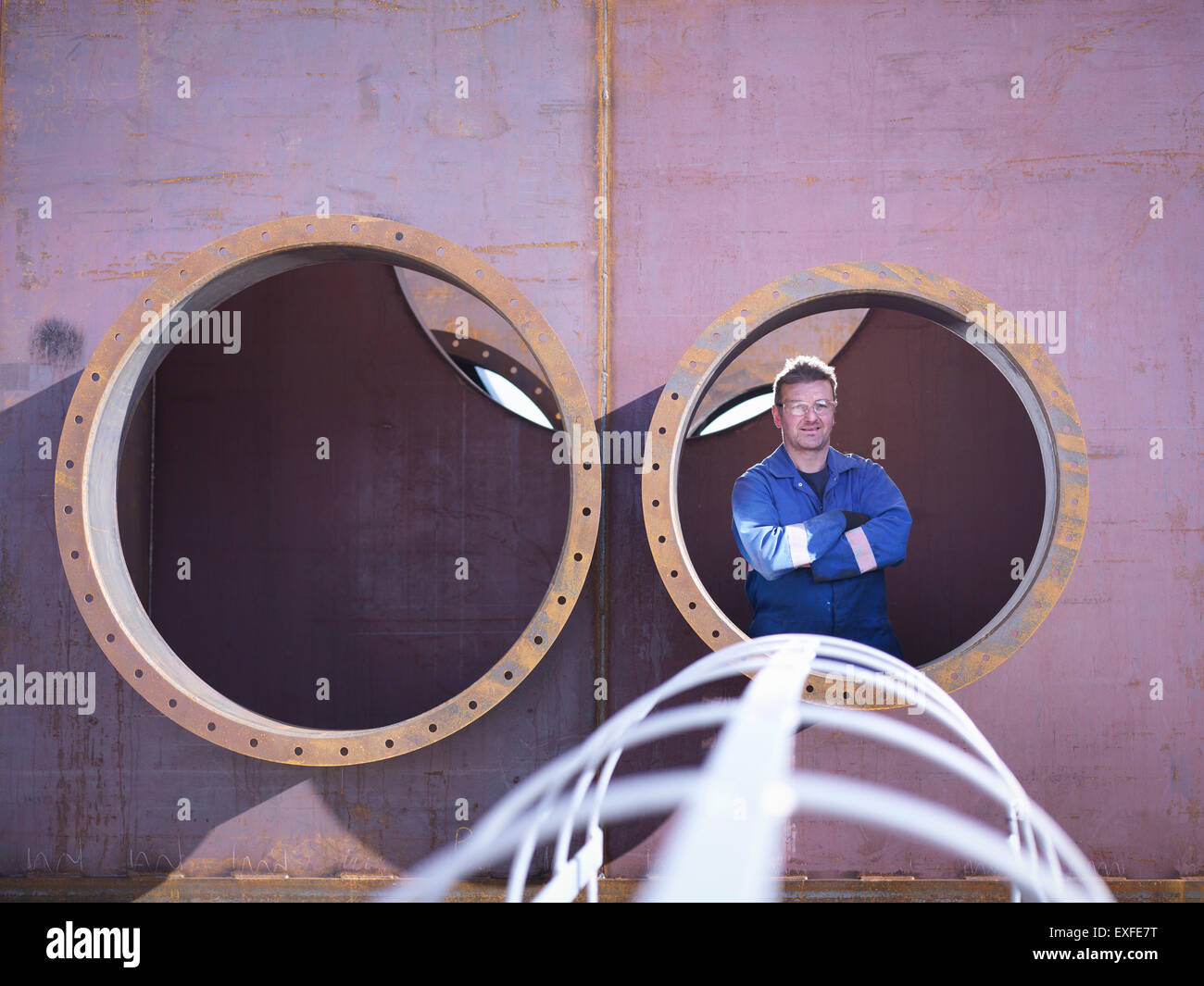 Portrait of engineer inside large steel superstructure in engineering factory - Stock Image