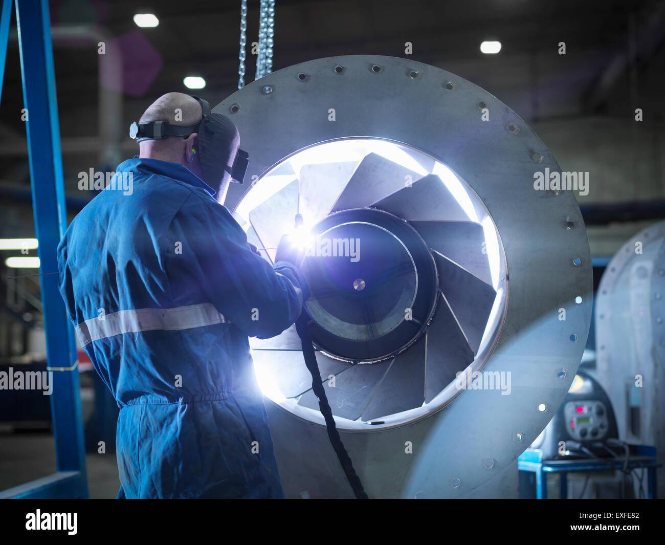 Engineer welding airduct part in engineering factory - Stock Image