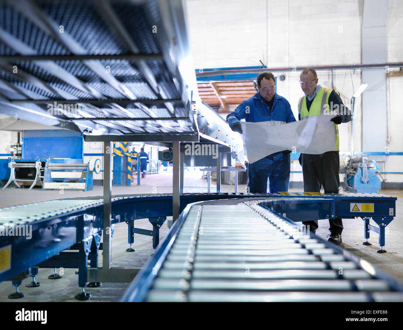 Engineers inspecting new conveyor in engineering factory - Stock Image