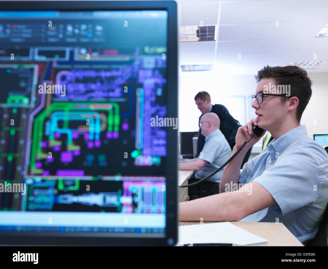 Engineers on phone and looking at CAD designs in engineering factory office - Stock Image