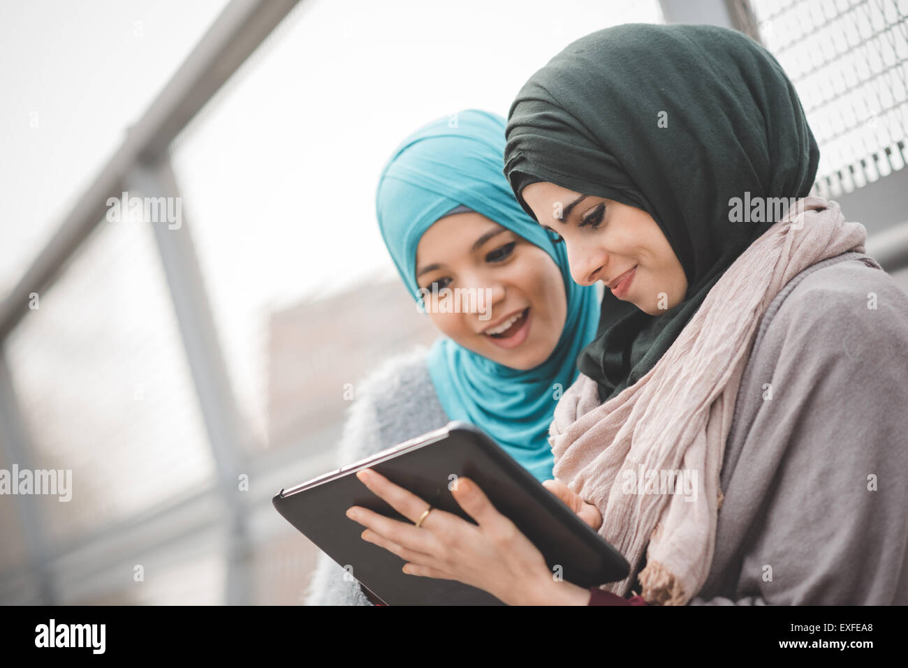 Two young women wearing hijabs using digital tablet on footbridge - Stock Image
