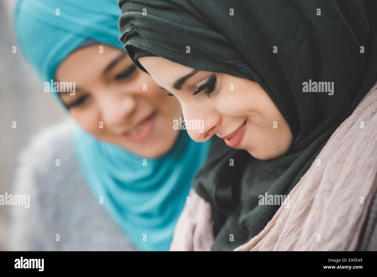 Close up of two young women wearing hijabs - Stock Image