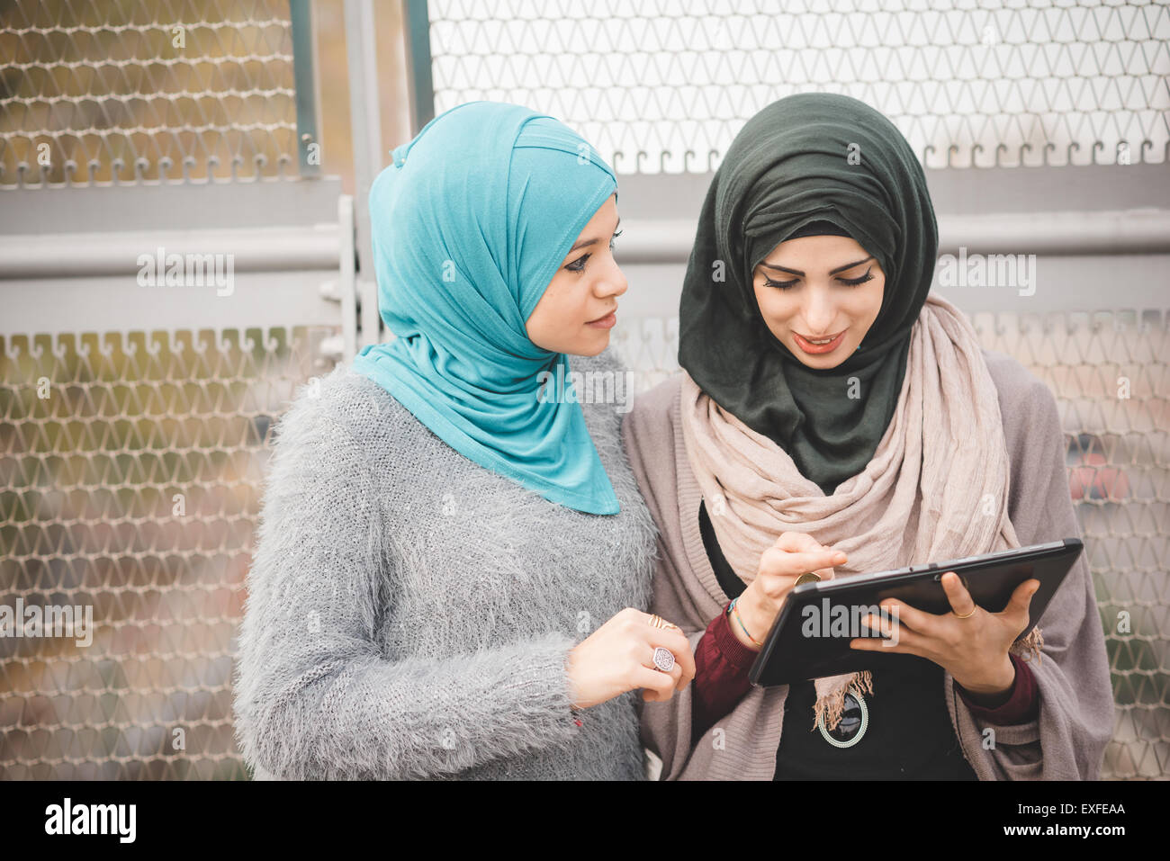 Two young women wearing hijabs using touchscreen on digital tablet on footbridge - Stock Image