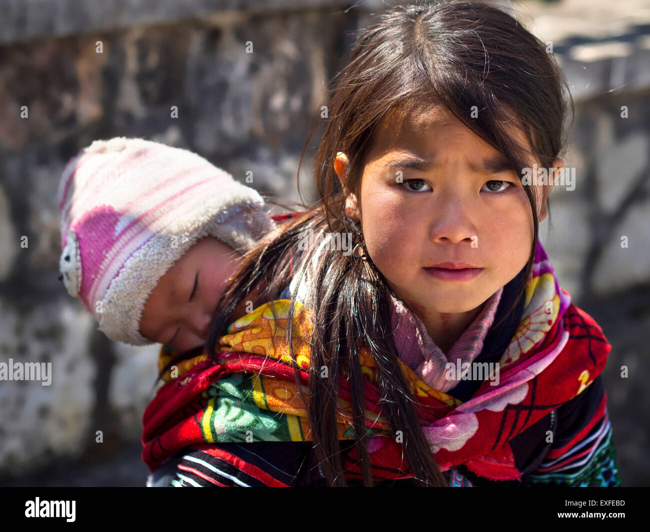 Unidentified Hmong girl carrying baby and wearing traditional attire in Sapa town, Lao Cai, Vietnam. - Stock Image