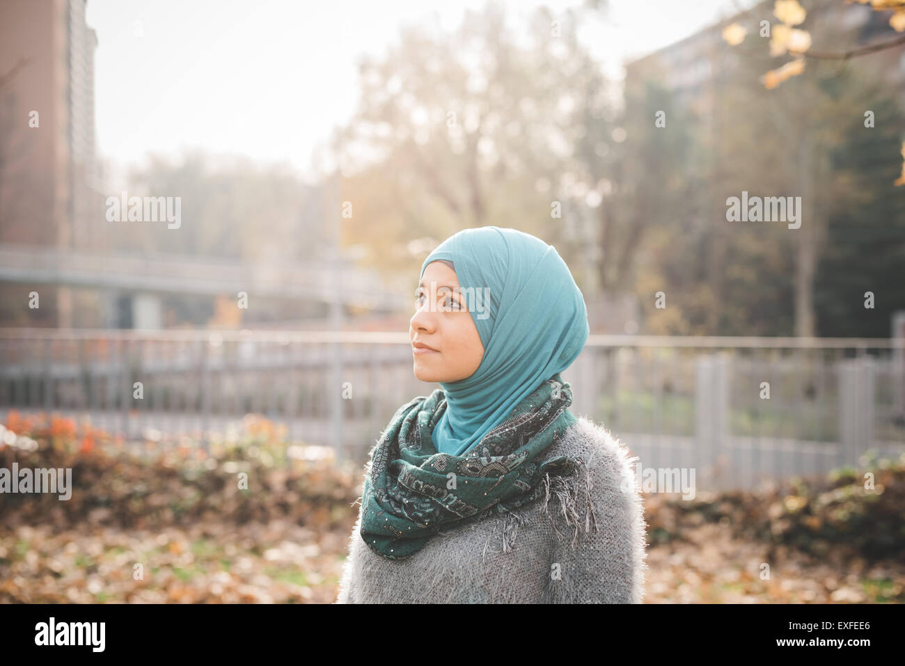 Portrait of young woman wearing hijab gazing in park - Stock Image