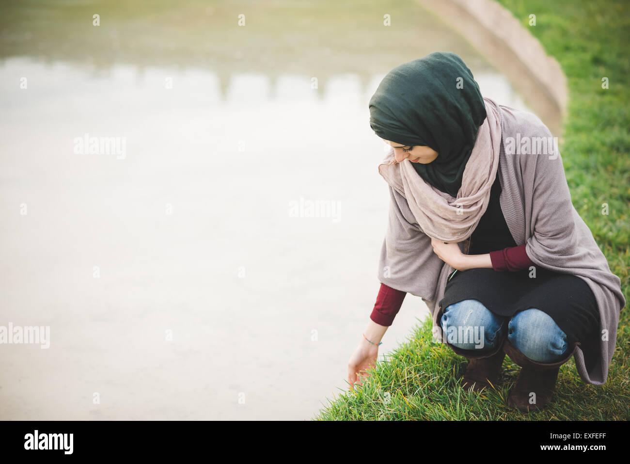 Young woman wearing hijab crouching next to park lake - Stock Image