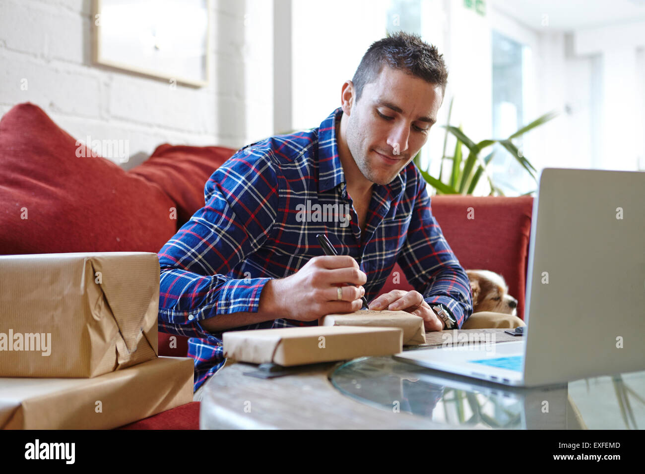 Mid adult man writing address on parcels in picture framers showroom - Stock Image