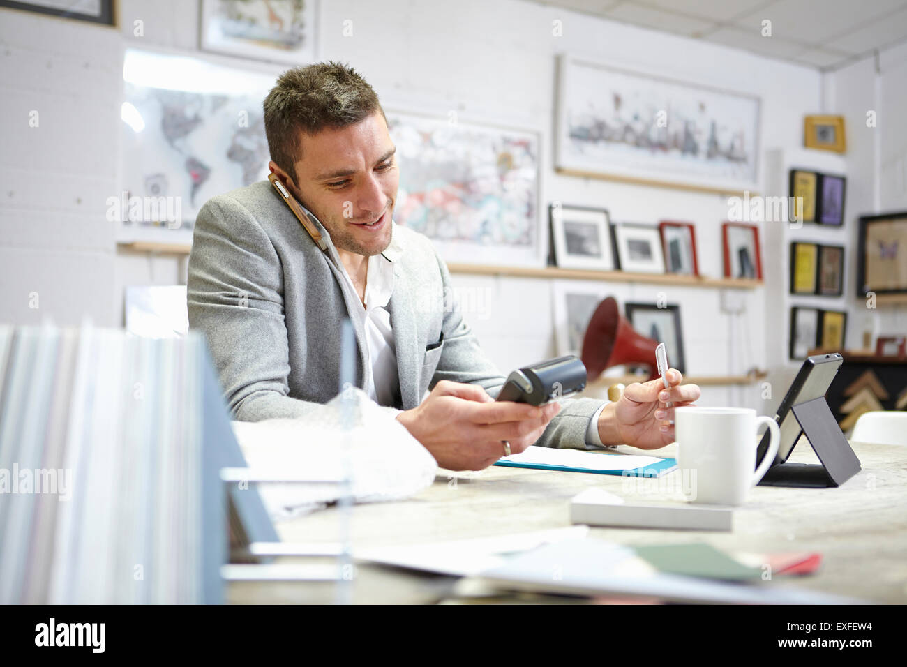 Man buying on smartphone with credit card reader in picture framers workshop Stock Photo