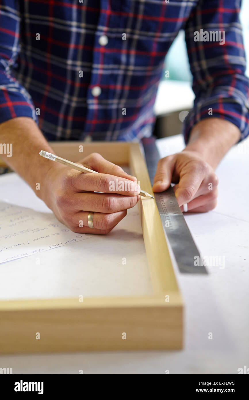 Close up of mid adult man measuring frame on workbench in picture framers workshop - Stock Image