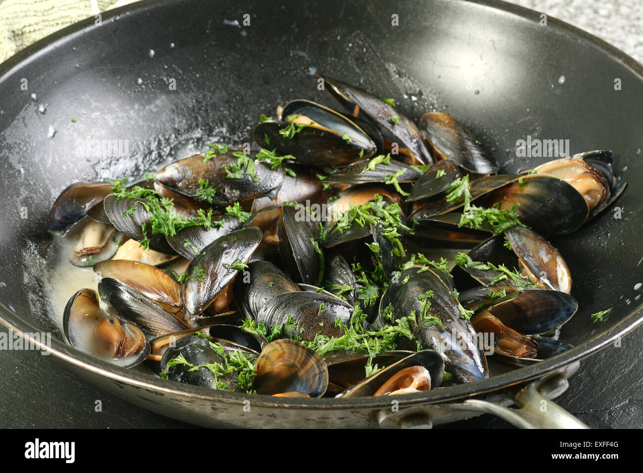 mussels cooked in a pan with white wine sauce - Stock Image