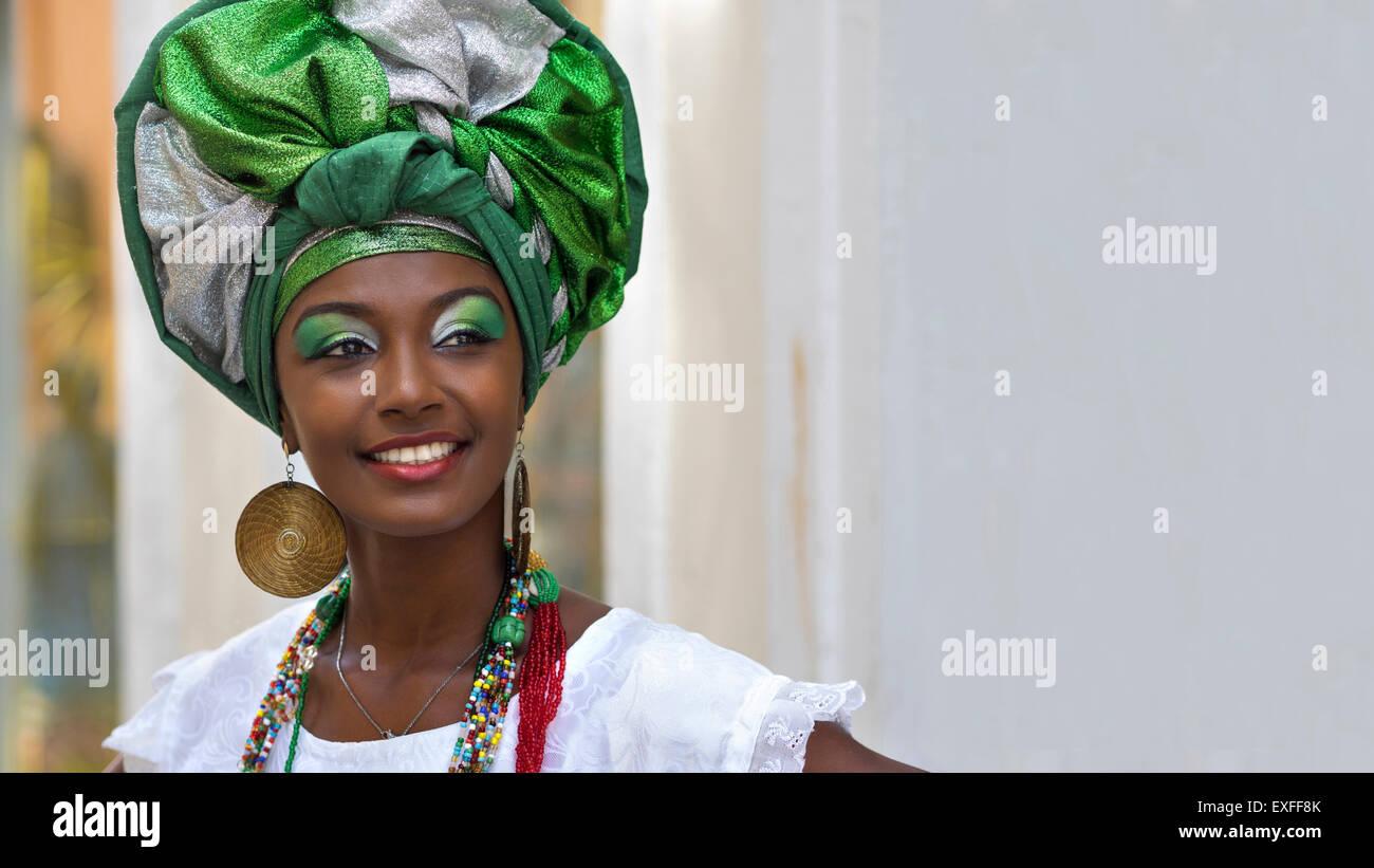 Baiana, smiling Brazilian woman of African descent, wearing traditional attire in Pelourinho, Salvador, Bahia, Brazil. - Stock Image