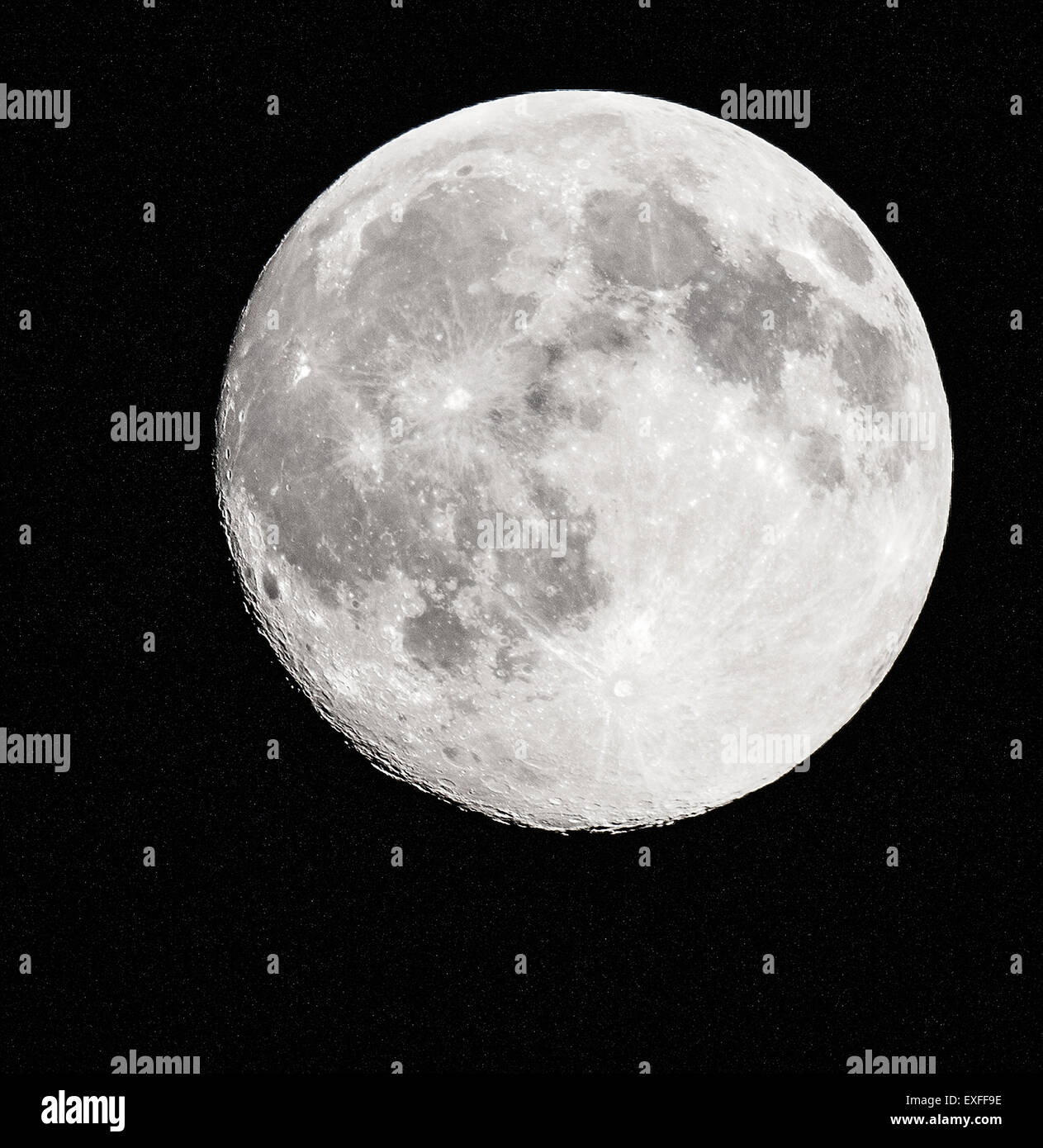 Full moon minus a few hours with a ragged crater lined edge and star speckled space behind - photographed in the Stock Photo