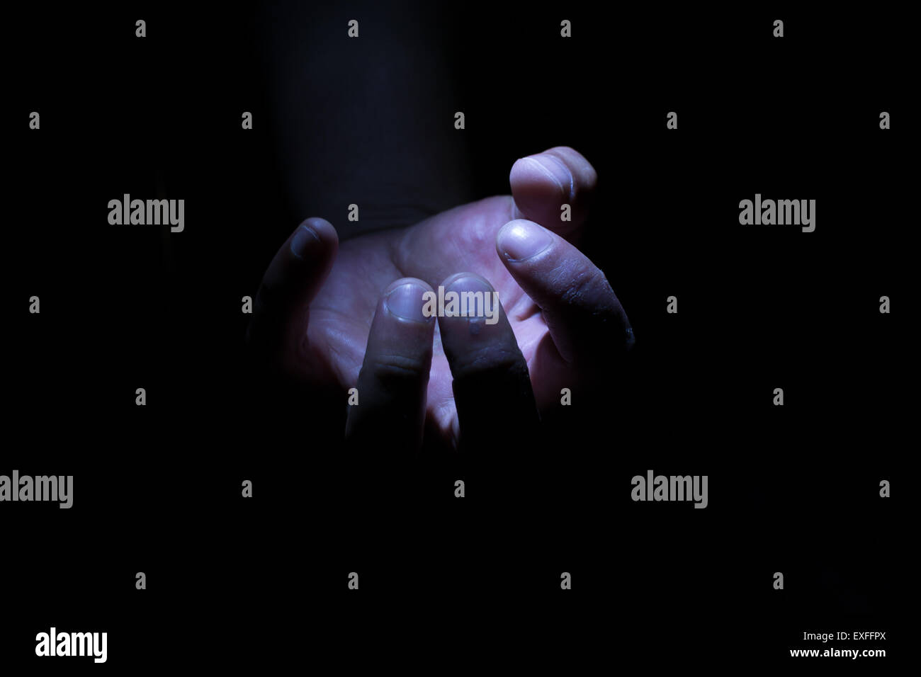 White male hand in darkness and shadow clutching an invisible empty item - Stock Image