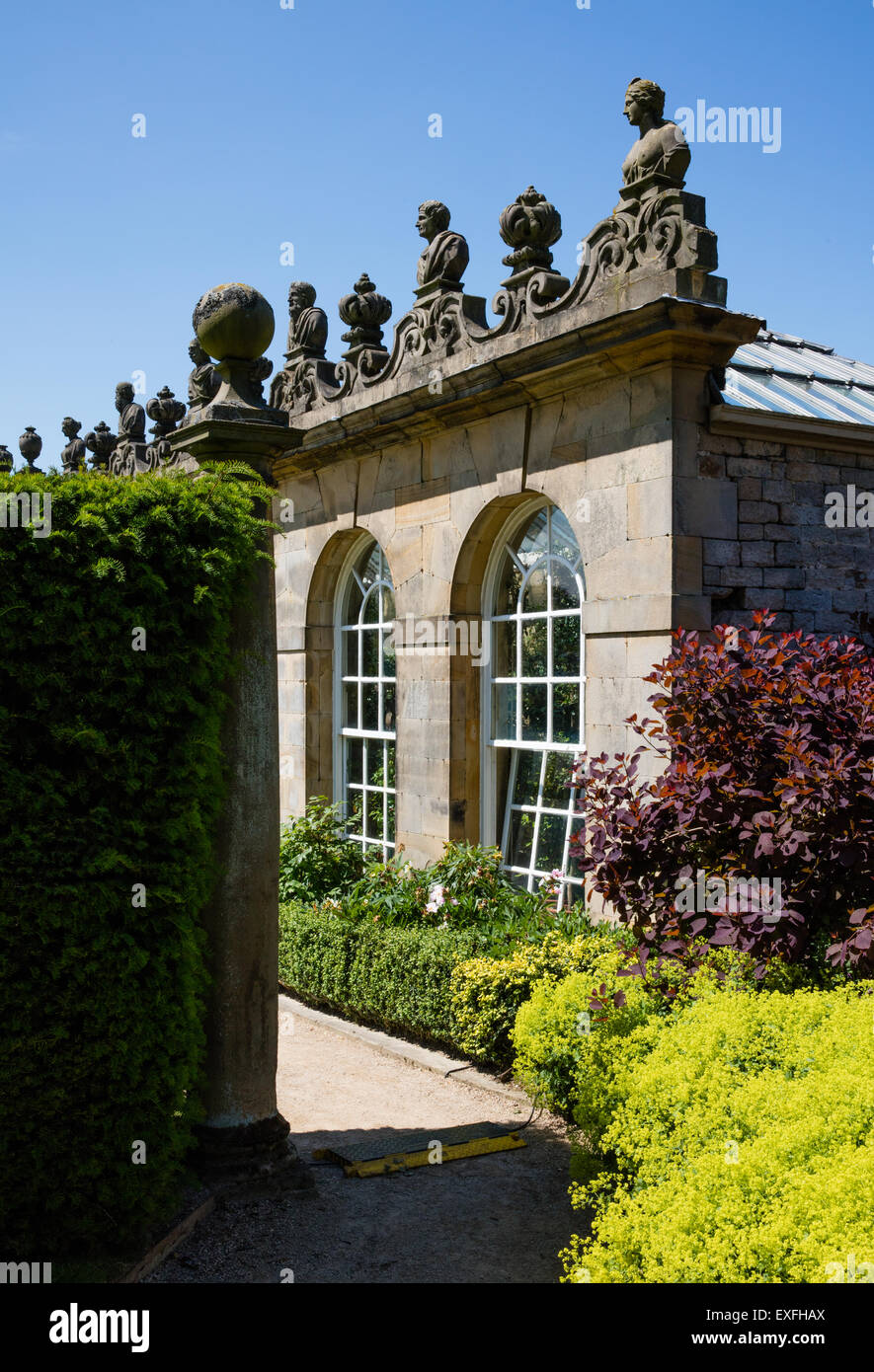 A glimpse of the First Dukes Greenhouse or Orangery backing the rose garden in Chatsworth Gardens Derbyshire Peak - Stock Image
