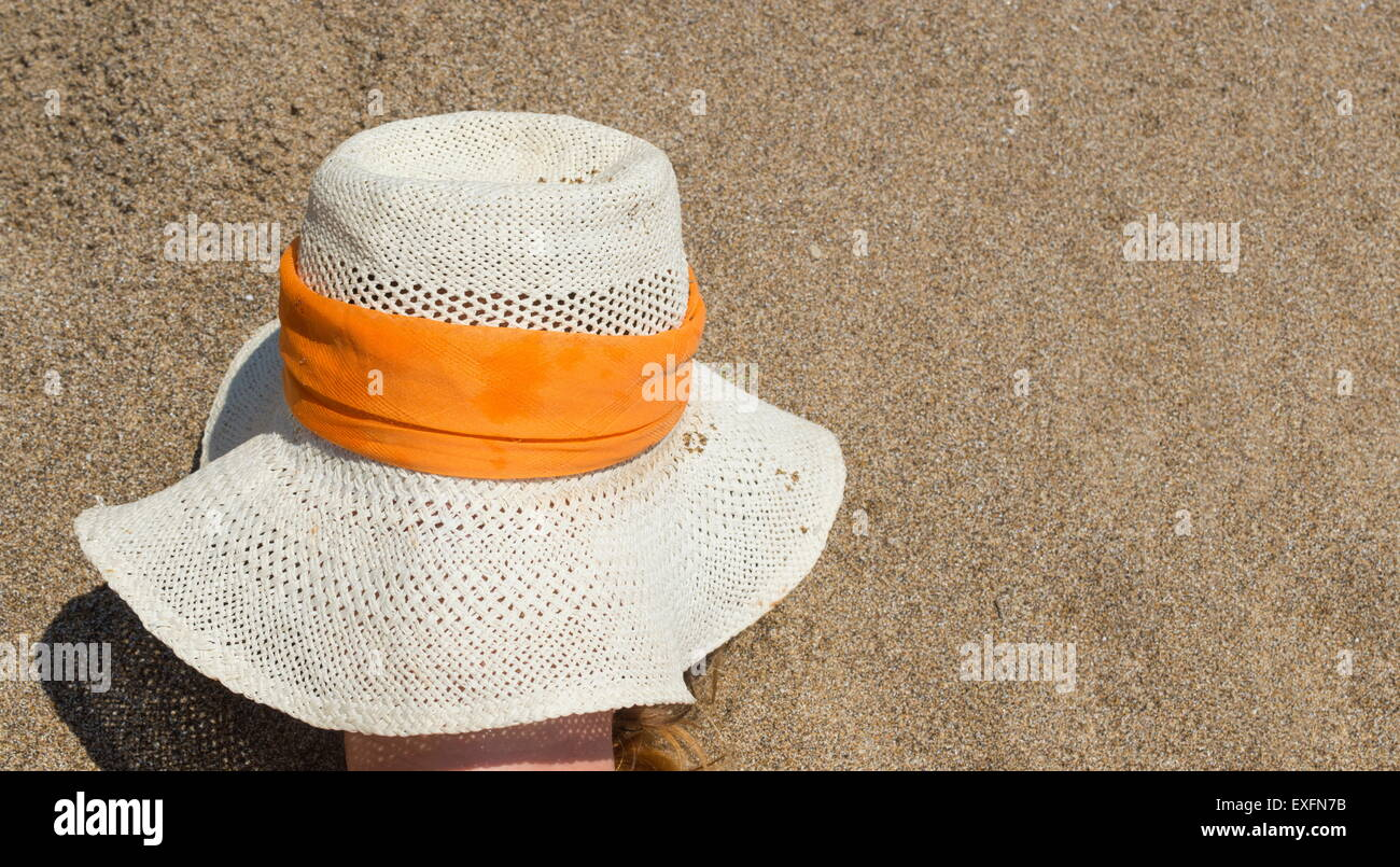 Girl covering her face on the beach to protect from the Sun - Stock Image