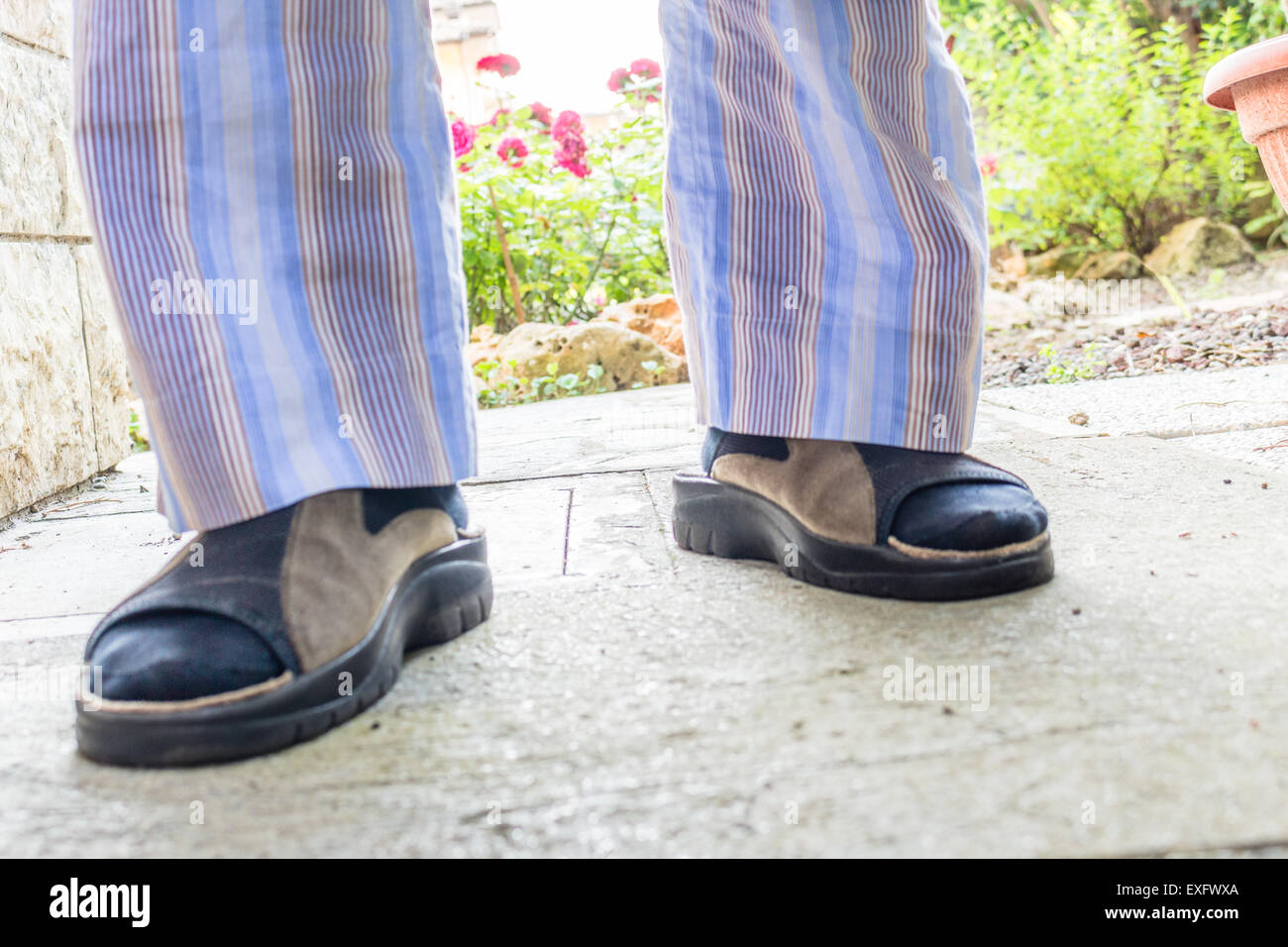 Feet Of Man In Brown Slippers With Blue Socks Blue Striped