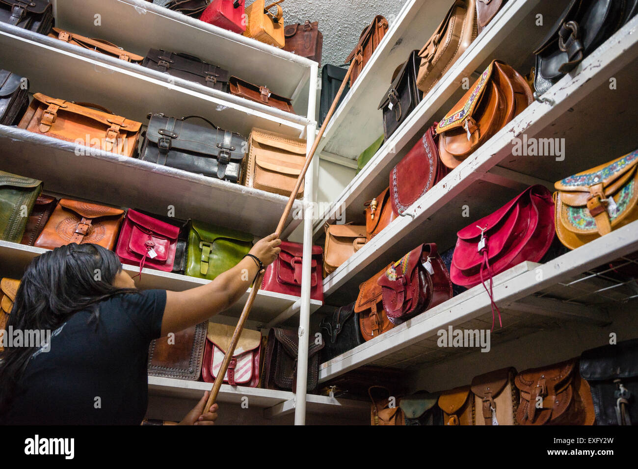 Woman reaching to get leather handbag from top shelf in a stall at a market in Oaxaca Mexico - Stock Image