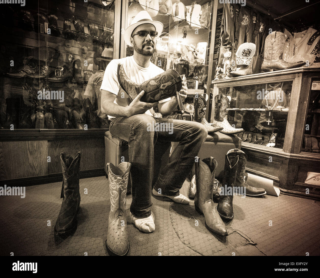 Hispanic man trying on stylish Mexican pointy boots in a store in Oaxaca Mexico - Stock Image