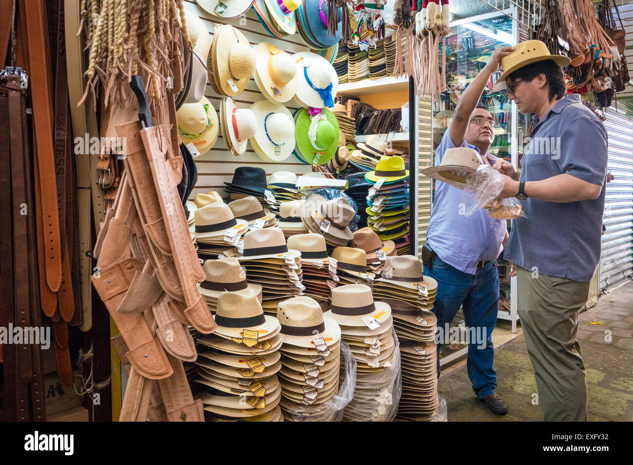 Salesman reaching to put a straw hat on a customer shopping at a market in Oaxaca Mexico - Stock Image