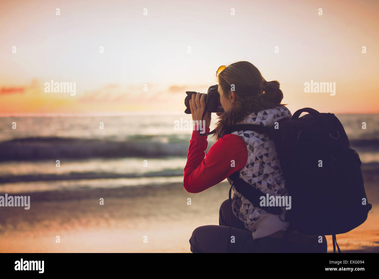 Girl photographer taking pictures with SLR camera at sunset on the beach - Stock Image