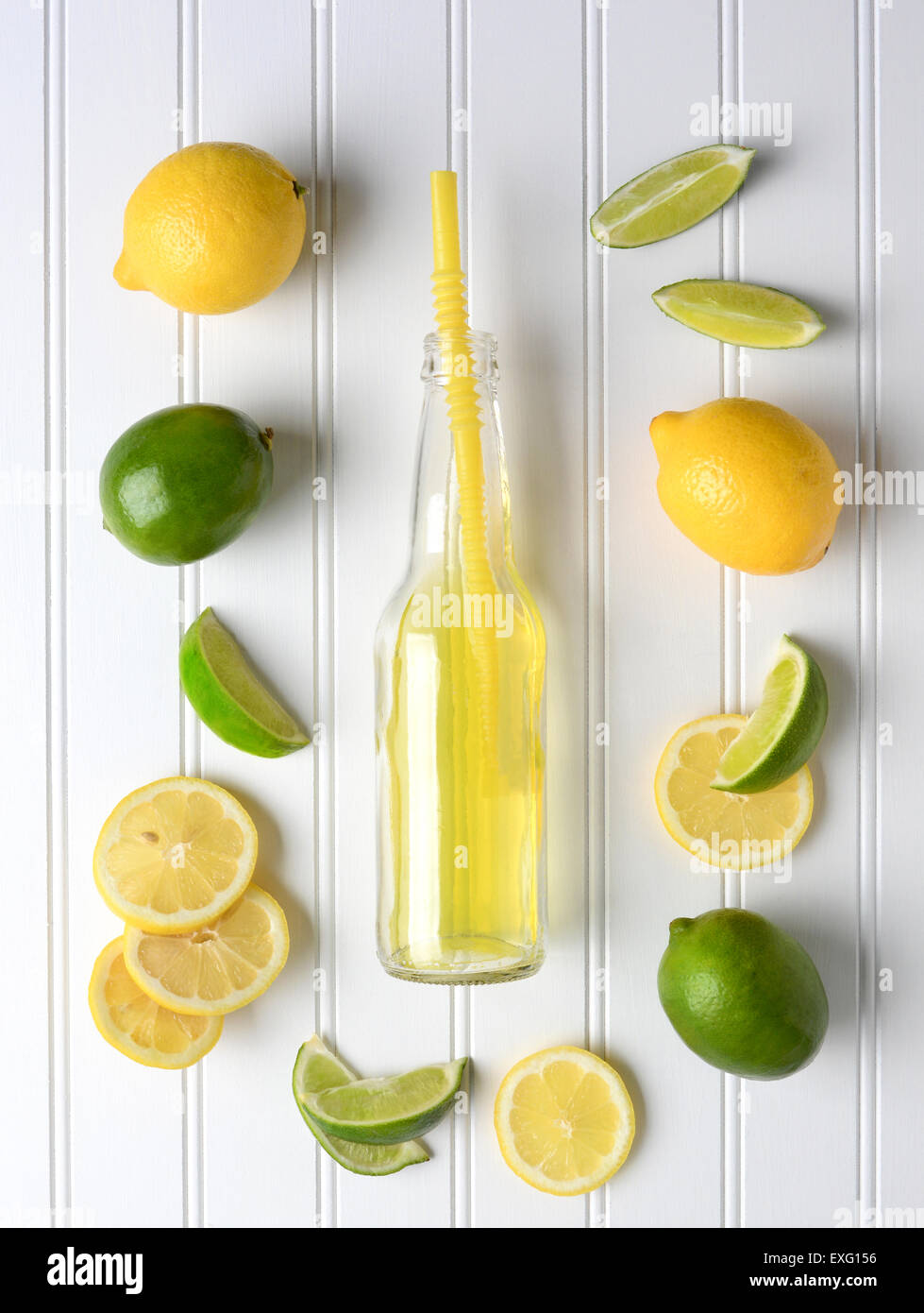 Limes and Lemons surrounding a bottle of soda on a white bead board table. High angle shot in vertical format. - Stock Image