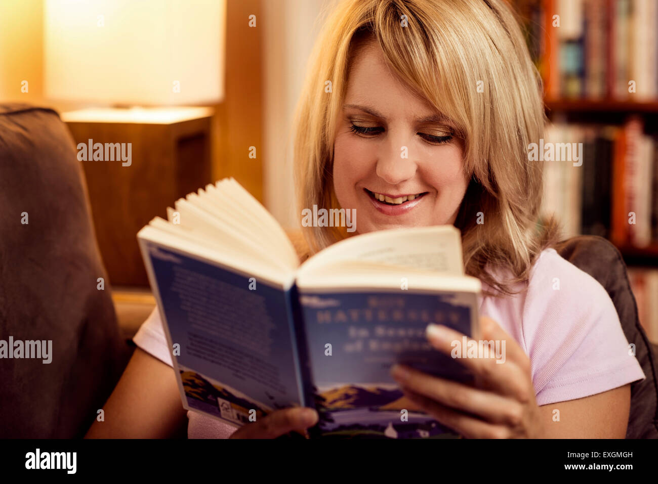 Woman reading book on sofa at home - Stock Image