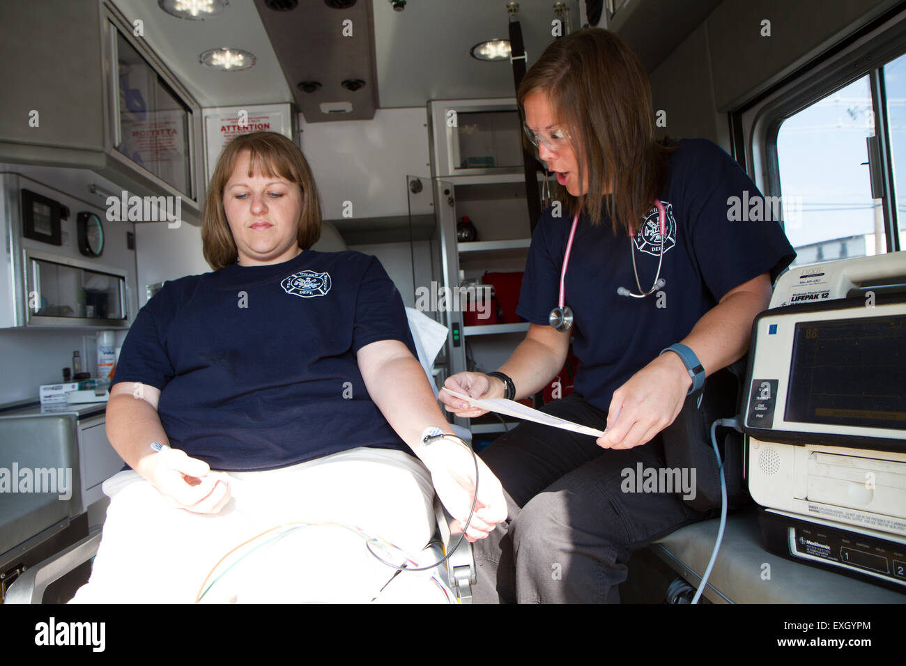 Female paramedics working in the back of an ambulance. Rural volunteer US fire department. - Stock Image