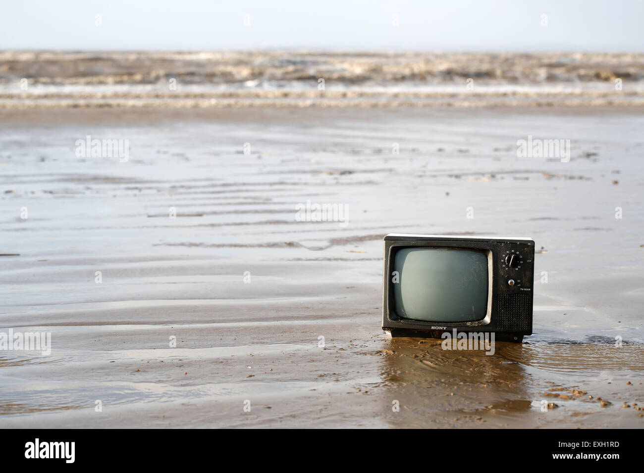 An old TV, washed up out of the sea onto an English sandy shoreline. Environmentally damaging to the beach at weston - Stock Image