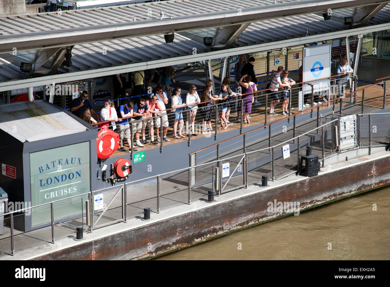 People Waiting on Cruise Boat on River Thames Pier in London UK - Stock Image