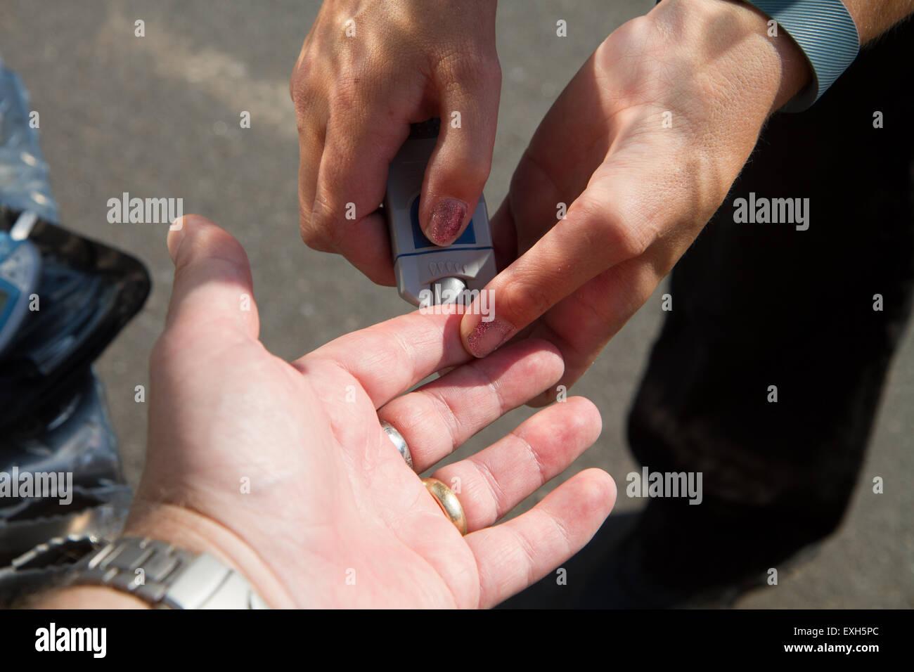 EMT / Paramedic administers blood sugar test in ambulance. - Stock Image