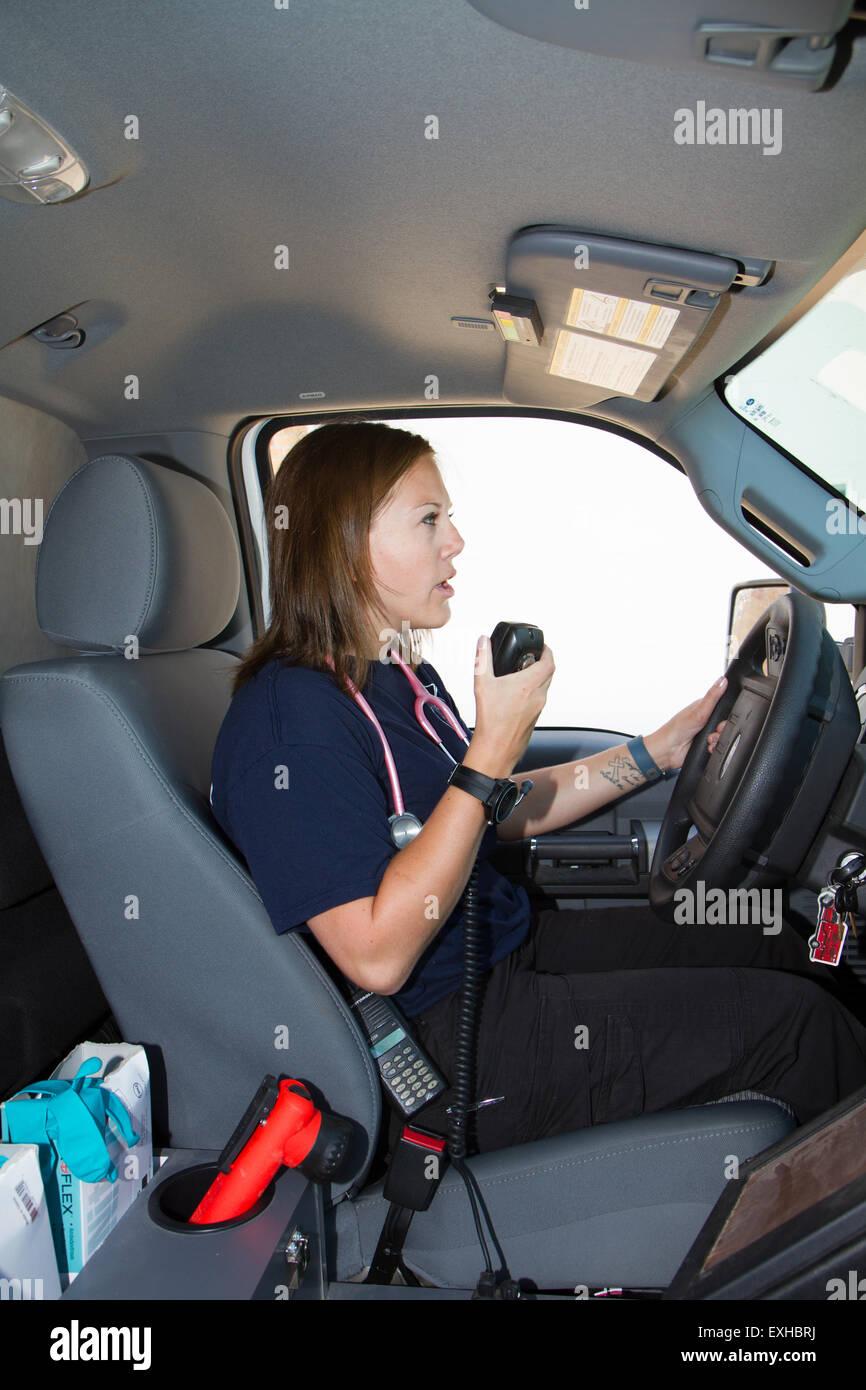 Female paramedic EMT using radio in ambulance. Rural volunteer fire department ambulance. - Stock Image