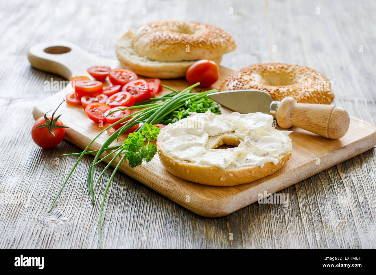 Bagels sandwiches with cream cheese, tomatoes and chives for healthy snack - Stock Image