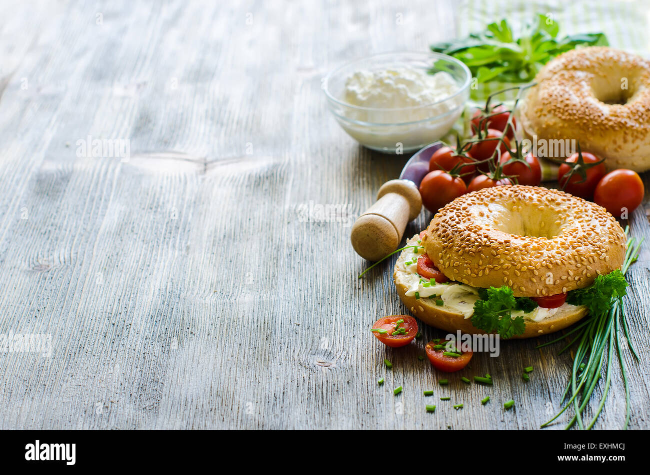 Bagels sandwiches with cream cheese, tomatoes and chives copy space - Stock Image